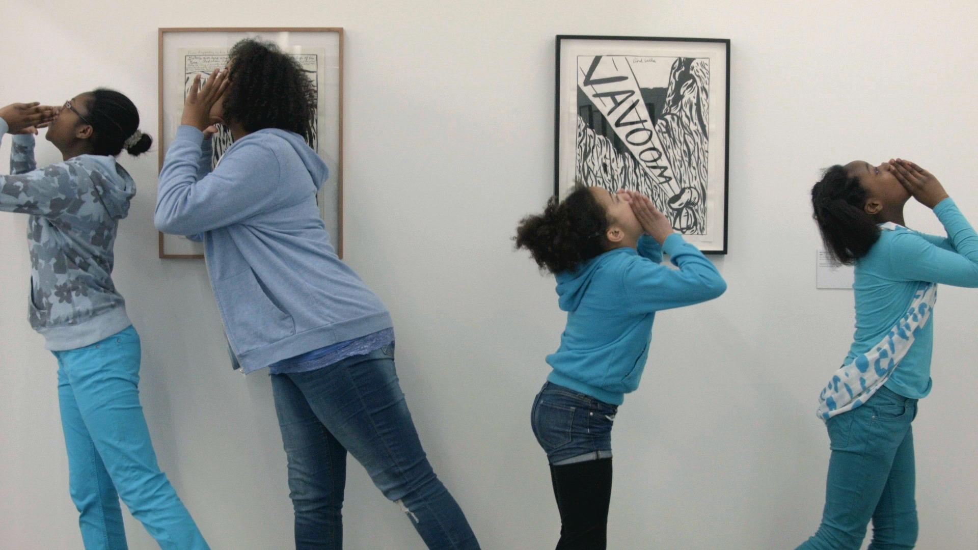 Vier Mädchen führen spontan einen darstellenden Tanz vor Gemälden von Raymond Pettibon in der Sammlung Falckenberg auf.